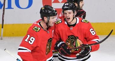 Blackhawks forward David Kampf (64) celebrates with center Jonathan Toews (19) after scoring a goal against the Canucks.
