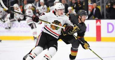 Blackhawks center Kirby Dach (77) skates against Golden Knights defenseman Jon Merrill (15).