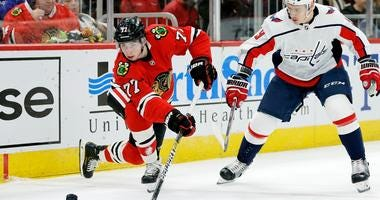 Blackhawks rookie forward Kirby Dach (77) and Capitals defenseman Dmitry Orlov (9) battle for the puck.