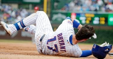 Cubs third baseman Kris Bryant (17) falls to the ground after suffering an ankle injury while stepping on first base as he was forced out for a double play against the Cardinals.