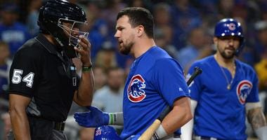 Cubs left fielder Kyle Schwarber (middle) talks to umpire CB Bucknor (54) after being called out on strikes.