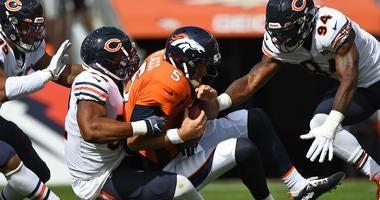 Bears outside linebacker Khalil Mack (52) and outside linebacker Leonard Floyd (94) sack Broncos quarterback Joe Flacco (5).