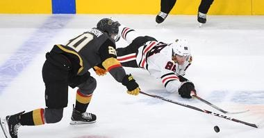 Blackhawks right wing Patrick Kane (88) tips the puck away from Golden Knights center Chandler Stephenson (20).