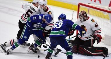 Canucks forward Loui Eriksson (21) and forward Bo Horvat (53) shoot the puck against Blackhawks goaltender Robin Lehner (40).