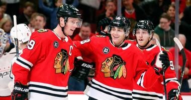 Blackhawks center Jonathan Toews (19) celebrates with teammate Patrick Kane (center) after scoring a goal.