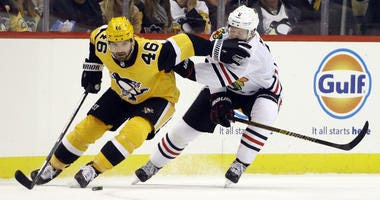 Blackhawks forward Brandon Saad, right, battles for the puck.