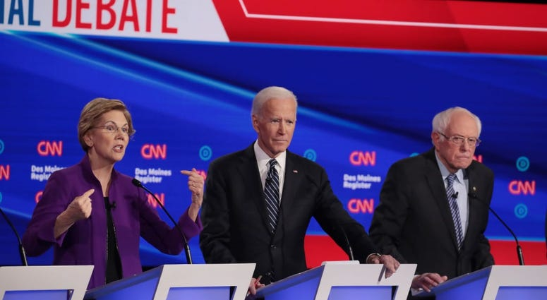 Sen. Elizabeth Warren (D-MA) speaks as former Vice President Joe Biden and Sen. Bernie Sanders (I-VT) (R) listen during the Democratic presidential primary debate at Drake University on January 14, 2020 in Des Moines, Iowa.