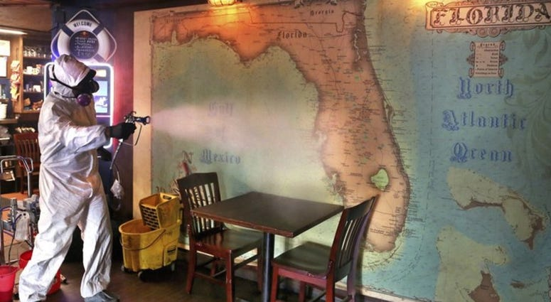 Eric Rodriguez, co-owner of Disinfectant Firm, Tampa, disinfects a map of Florida using Proxitane AHC at The Galley tavern in St. Petersburg, Fla., Wednesday, June 24, 2020.