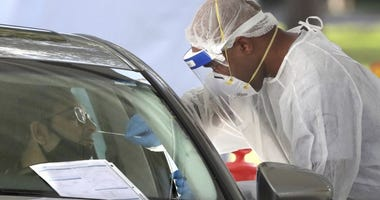 A medical professional applies a nasal swab during testing at the Orange County Health Services COVID-19 drive-thru site at Barnett Park in Orlando, Fla., Thursday, Oct. 29, 2020.