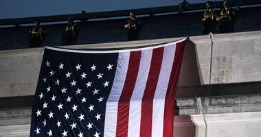 An American flag is unfurled down the side of the Pentagon to mark the 17th anniversary of the 9/11 terror attacks in Arlington, Virginia.