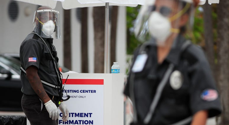 Security guards look on from the City of Miami Beach's municipal parking lot located at 4621 Collins Avenue which houses a MedRite COVID-19 testing site on April 05, 2020 in Miami Beach, Florida.