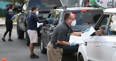 Workers hand out unemployment applications to people in their vehicles in Hialeah, Florida. The city is distributing the printed unemployment forms to residents as people continue to have issues with access to the state of Florida's unemployment website.