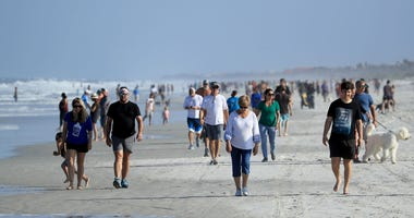 People at Jacksonville Beach April 17, 2020. Mayor Lenny Curry announced Duval County's beaches would open at 5pm, but only for restricted hours and can only be used for swimming, running, surfing, walking, biking, fishing, and taking care of pets.