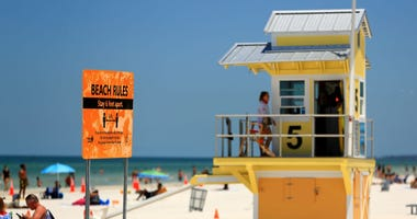 A sign displays the rules as people visit Clearwater Beach after Governor Ron DeSantis opened the beaches at on May 04, 2020 in Clearwater, Florida.