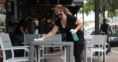Maria Iraola wipes down the sidewalk tables of the Argentino Las Olas restaurant as it prepares to open to customers in Fort Lauderdale, Florida.