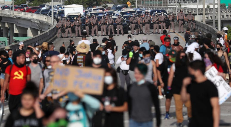 Police watch as demonstrators march onto the freeway during a protest against police brutality and the recent death of George Floyd, on May 31, 2020 in Miami, Florida.