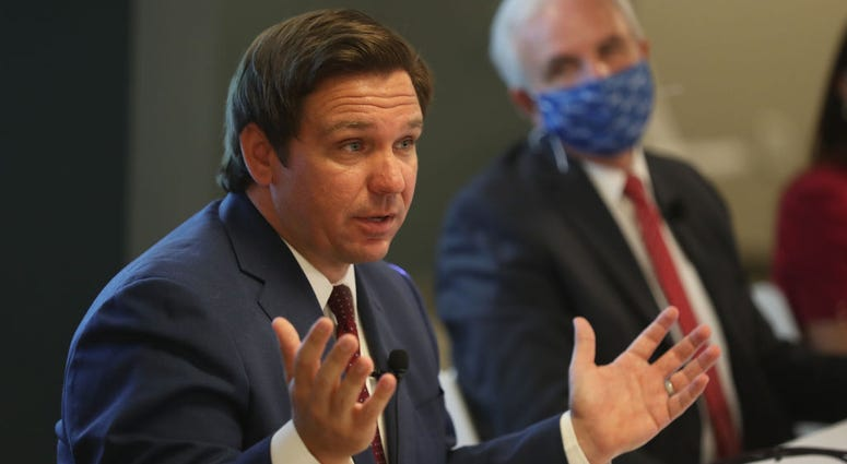 Florida Governor Ron DeSantis, seated next to Mayor of Miami-Dade Carlos A. Gimenez (R), speaks during a press conference about the coronavirus held at the Pan American Hospital on July 07, 2020 in Miami, Florida.
