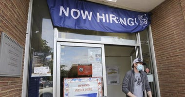 Customer walks out of a U.S. Post Office branch and under a banner advertising a job opening. The U.S. government issued its latest snapshot Thursday, June 18, of the layoffs that have left millions unemployed.