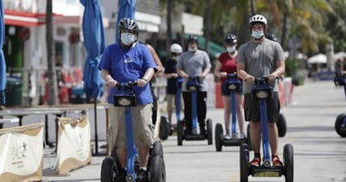 A tour group riding Segways rides down Miami Beach, Florida's famed Ocean Drive on South Beach, July 4, 2020.