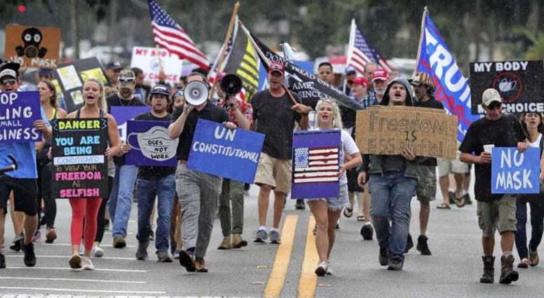 Demonstrators march through downtown Sanford, Fla., July 1, 2020, to protest a Seminole County order requiring people to wear masks in response to the spike in coronavirus cases.