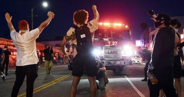 Demonstrators block the path of a Los Angeles Fire Department truck during a public disturbance Saturday, May 30, 2020, in Los Angeles. Protests were held in U.S. cities over the death of George Floyd in Minneapolis, Minn.