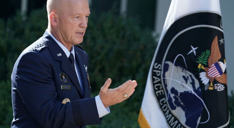 "U.S. Air Force Space Command Gen. John ""Jay"" Raymond stands next to the flag of the newly established U.S. Space Command, the sixth national armed service, in the Rose Garden at the White House August 29, 2019 in Washington, DC."