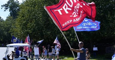 Trump supporters waive flags outside of Trump's resort in Sterling, Va.