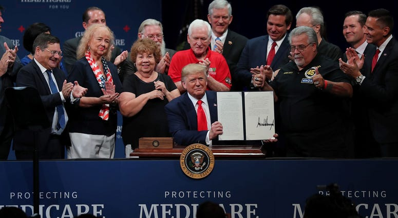 President Donald Trump sits at a table to sign an executive order concerning Medicare during an event at the Sharon L. Morse Performing Arts Center on October 03, 2019 in The Villages, Florida.