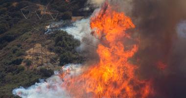 Tall flames rise near a high voltage power line tower at the Blue Cut Fire near Wrightwood, California.