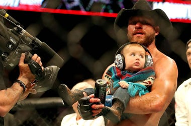 """Donald """"Cowboy"""" Cerrone holds his infant son after defeating Al Iaquinta at UFC Fight Night in Ottawa."""