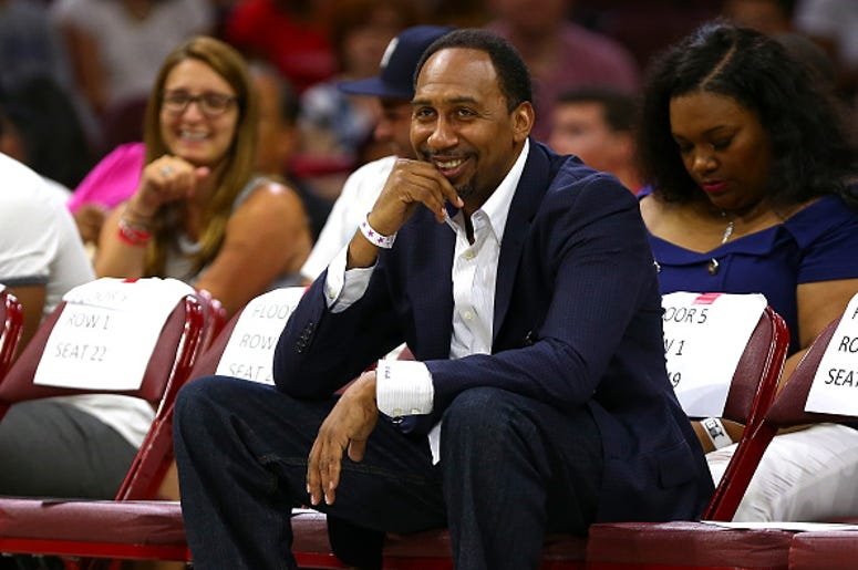 Stephen A. Smith watches a basketball game courtside.