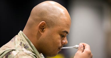 Military personnel, including Brandon Lawrence from Tacoma, Washington seen checking the accuracy of a thermometer, sets up the 627th Hospital Center field hospital at CenturyLink Event Center on March 31, 2020 in Seattle, Washington.