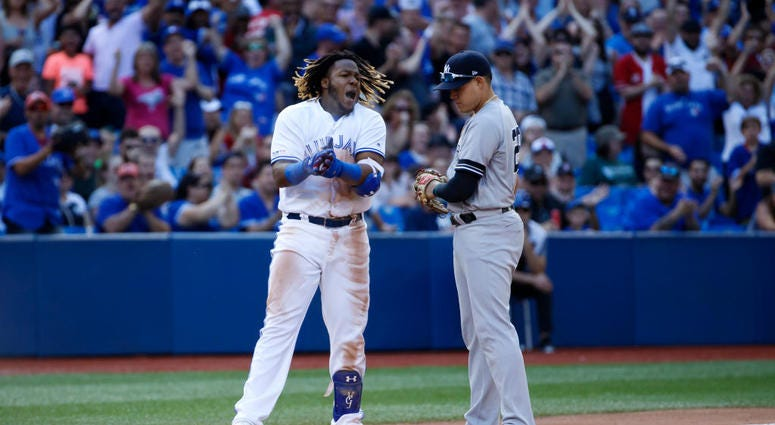 TORONTO, ON - AUGUST 10: Vladimir Guerrero Jr. #27 of the Toronto Blue Jays reacts as he is held at third base by Gio Urshela #29 of the New York Yankees after hitting a triple, allowing 2 runs in the 7th inning during MLB action against the New York Yank
