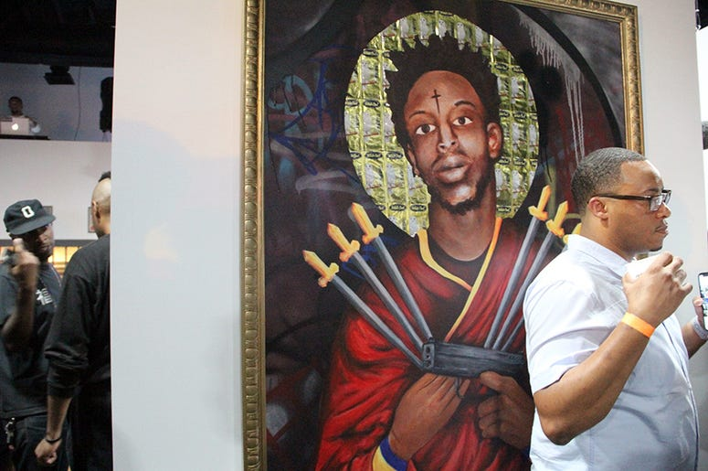 A man stands near a painting of Atlanta trap artist 21 Savage