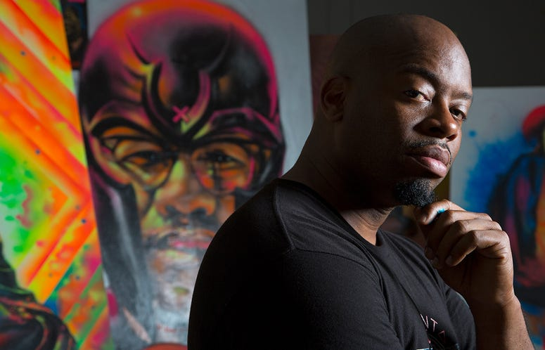 Fabian Williams poses in front of one of his paintings
