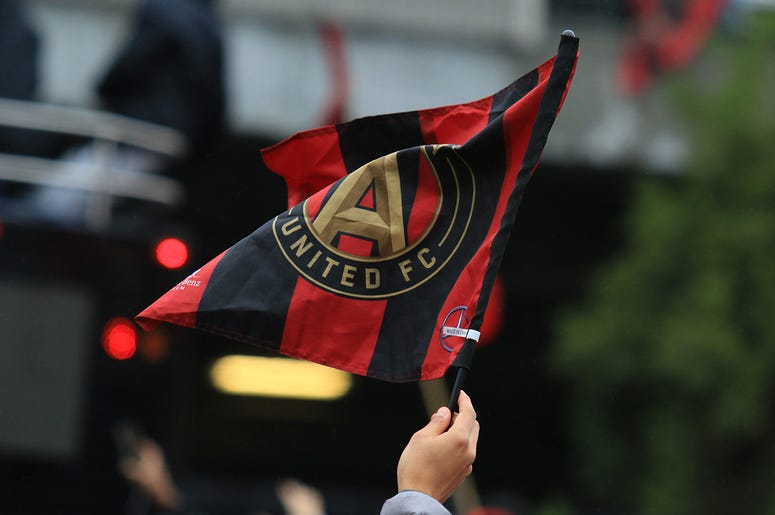 An Atlanta United fan waves the team flag during MLS Cup victory parade