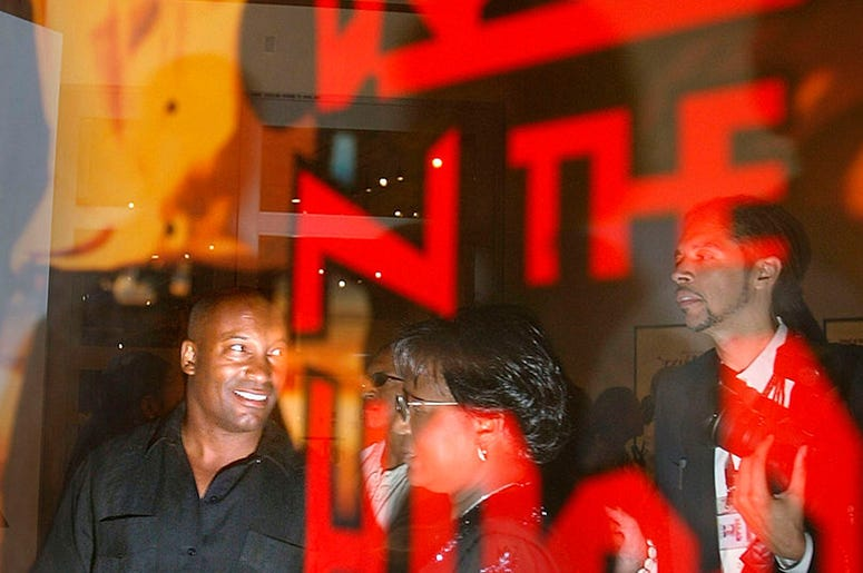 Director John Singelton (l) is reflected in a poster for his movie Boyz n the hood as he visits an exibition of African American film posters at the California African American Museum August 8, 2003 in Los Angeles.