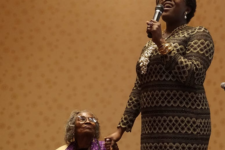 Mrs. Juanita Abernathy is serenaded by singer Nia Sadé Akinyemi during an awards ceremony in February 2019