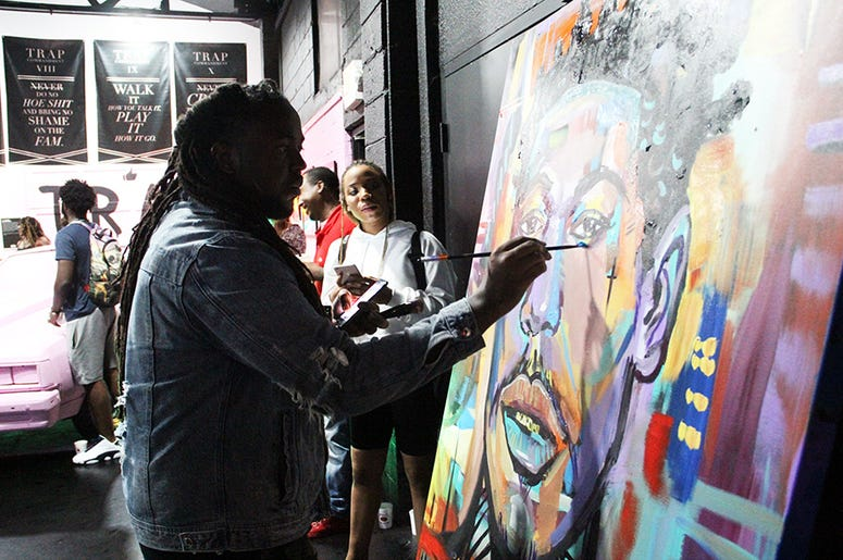 An artist creates a live painting of trap artist Kodak Black inside T.I.'s Trap Music Museum