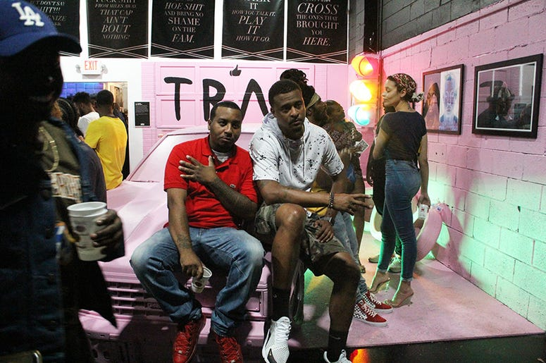 Attendees of T.I.'s Trap Music Museum preview event sit on 2 Chainz's pink Chevrolet