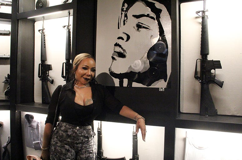 Tiny poses near a painting of T.I. in the rapper's personal area of his Trap Music Museum