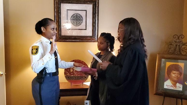 Melody Maddox is sworn in as sheriff by DeKalb Superior Court Judge LaTisha Dear Jackson as Maddox's daughter Indira Woodward looks on