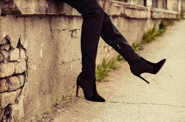 A young lady wears black high heel boots outdoors
