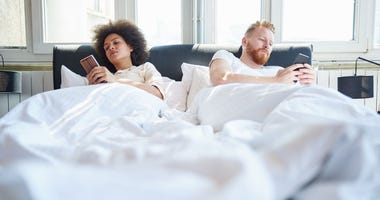 Couple using mobile phones in bed