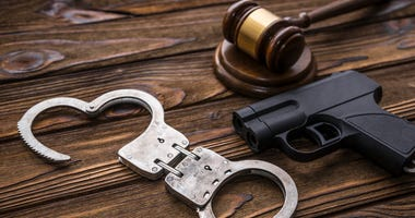 A gavel, gun and handcufffs