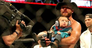 "Donald ""Cowboy"" Cerrone holds his infant son after defeating Al Iaquinta at UFC Fight Night in Ottawa."