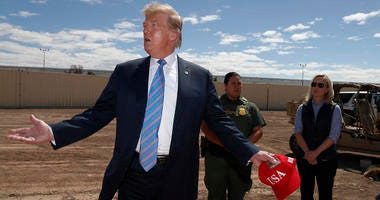 President Donald Trump visits a new section of the border wall with Mexico