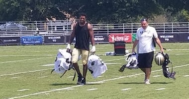 Saints rookie DE Marcus Davenport carries his equipment off the field after day 3 of training camp practice