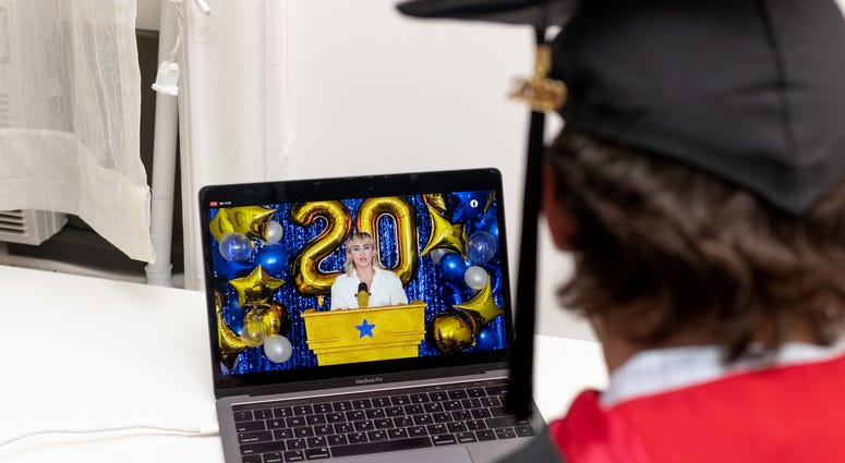 A recent graduate watches Miley Cyrus perform during a virtual graduation ceremony held by Facebook from his laptop on May 15, 2020 in New York City.