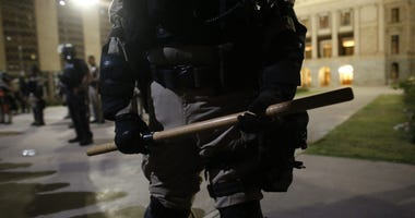 Police armed with batons stand outside the State Capitol as protesters chant during a Justice for George Floyd rally in downtown Phoenix, Ariz. on May 28, 2020. Justice For George Floyd Rally